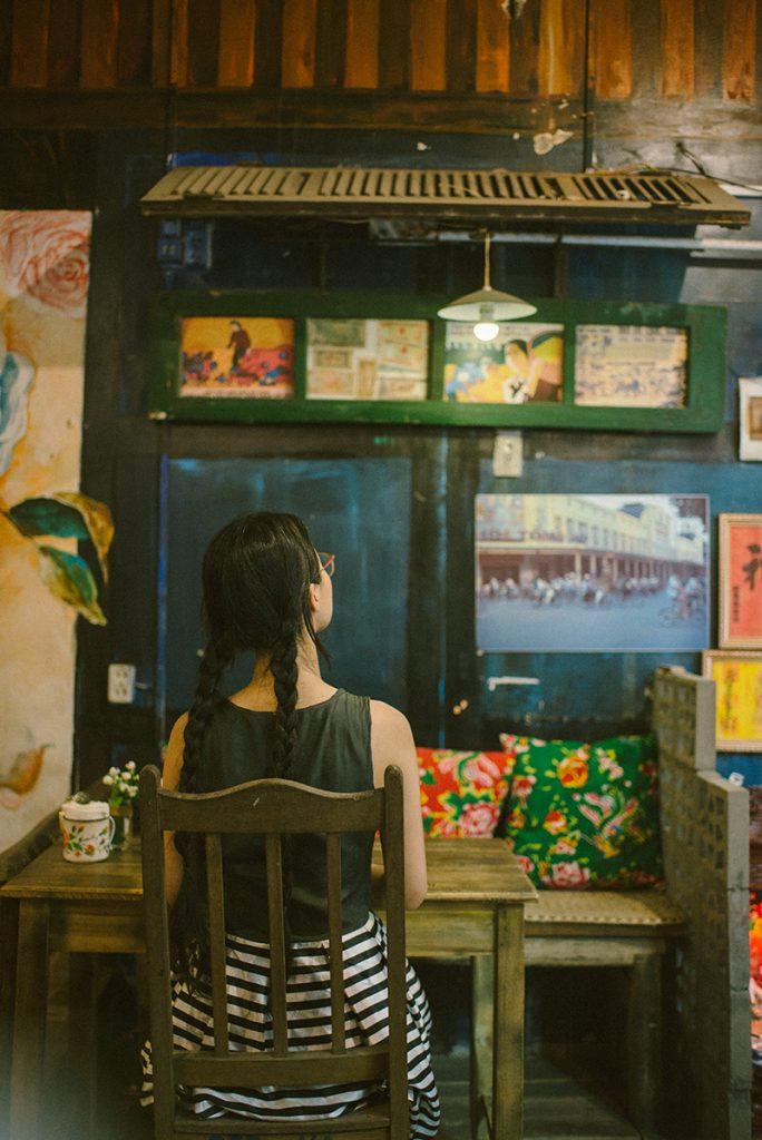 Quán cafe như một căn hộ tập thể thời bao cấp từ diện tích chật hẹp, bàn ghế gỗ nhỏ, đệm ghế được làm từ vỏ chăn con công, cánh cửa gỗ sờn màu, chiếc ti vi đỏ,...